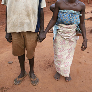 A man and a women hold hands. Their faces are not shown.