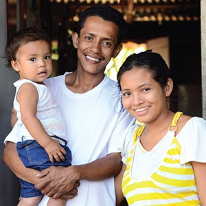 A Nicaraguan man and woman stand together smiling, and the man holds a young girl in his arms.