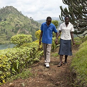 A Rwandan man walks outside with a woman on a dirt path, holding her hand. She is smiling and he is listening to her.