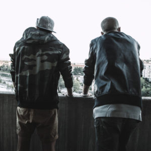 Two young men look over a balcony, their backs turned to the camera.