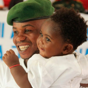 A smiling father holds his child at a Living Peace celebration.