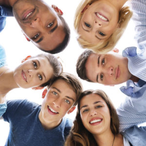 Six adolescent boys and girls stand in a circle, looking down at the camera and smiling.