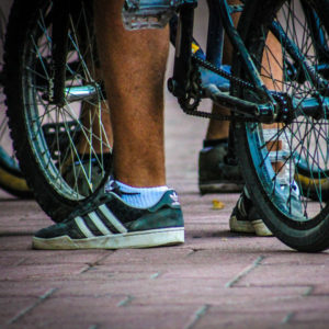 Close-up of a foot next to a bike.