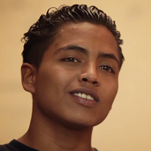 Headshot of Carlos, a young Nicaraguan man, speaking against a yellow background