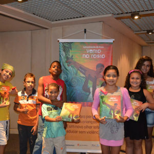 "Children stand together holding copies of the ""Vento No Rosto"" children's book."