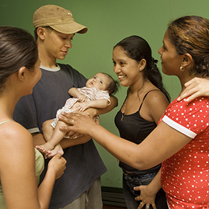 A young man in Brazil holds a baby while smiling, and three young women stand around him in a circle, talking.