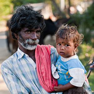 An Indian man holds his baby daughter in his arms.