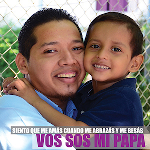 """A smiling father in Nicaragua holds his young son in his arms. The caption in Spanish reads: """"Siento que me amás cuando me abrazás y me besás. Vos sos mi papá."""""""