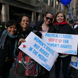 "Promundo staff and partners hold signs that say ""Women's voices, not bodies, in the media!"" and ""Political leaders, step it up for women's rights!"""