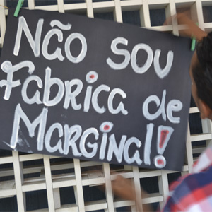 "A boy looks at a black sign that says ""Não sou Fabrica de Margina"""