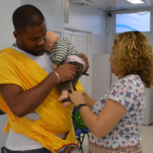 A father learns how to carry a baby in a sling, using a doll, in a MenCare+ workshop in Brazil.