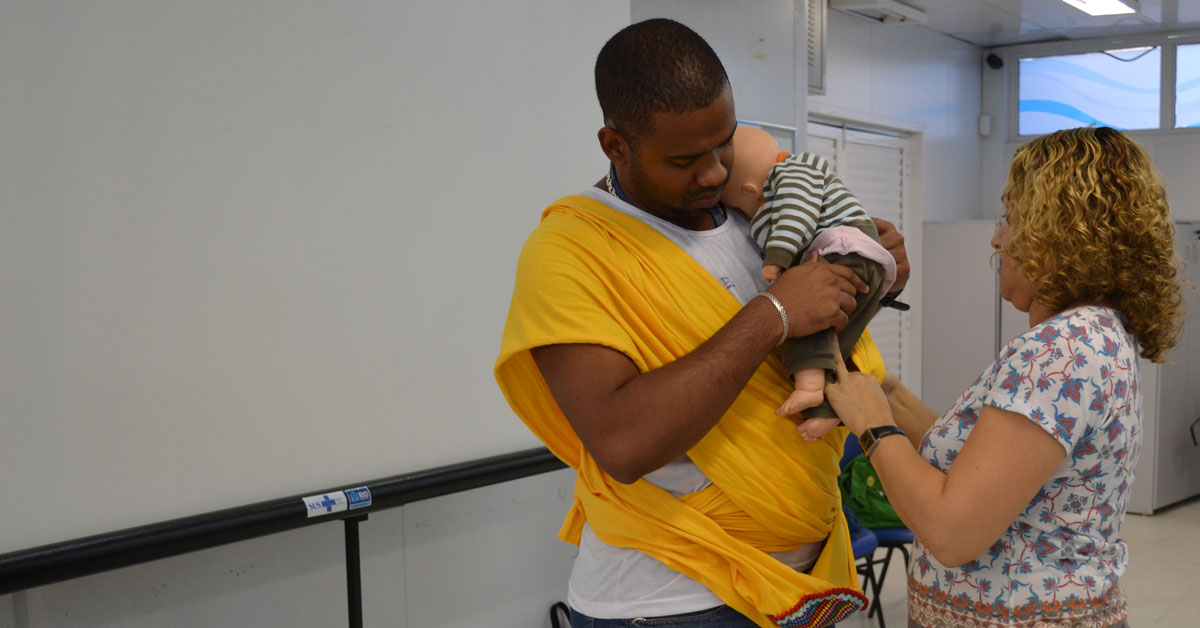MenCare-Plus-BrazA father learns how to carry a baby in a sling, using a doll, in a MenCare+ workshop in Brazil.